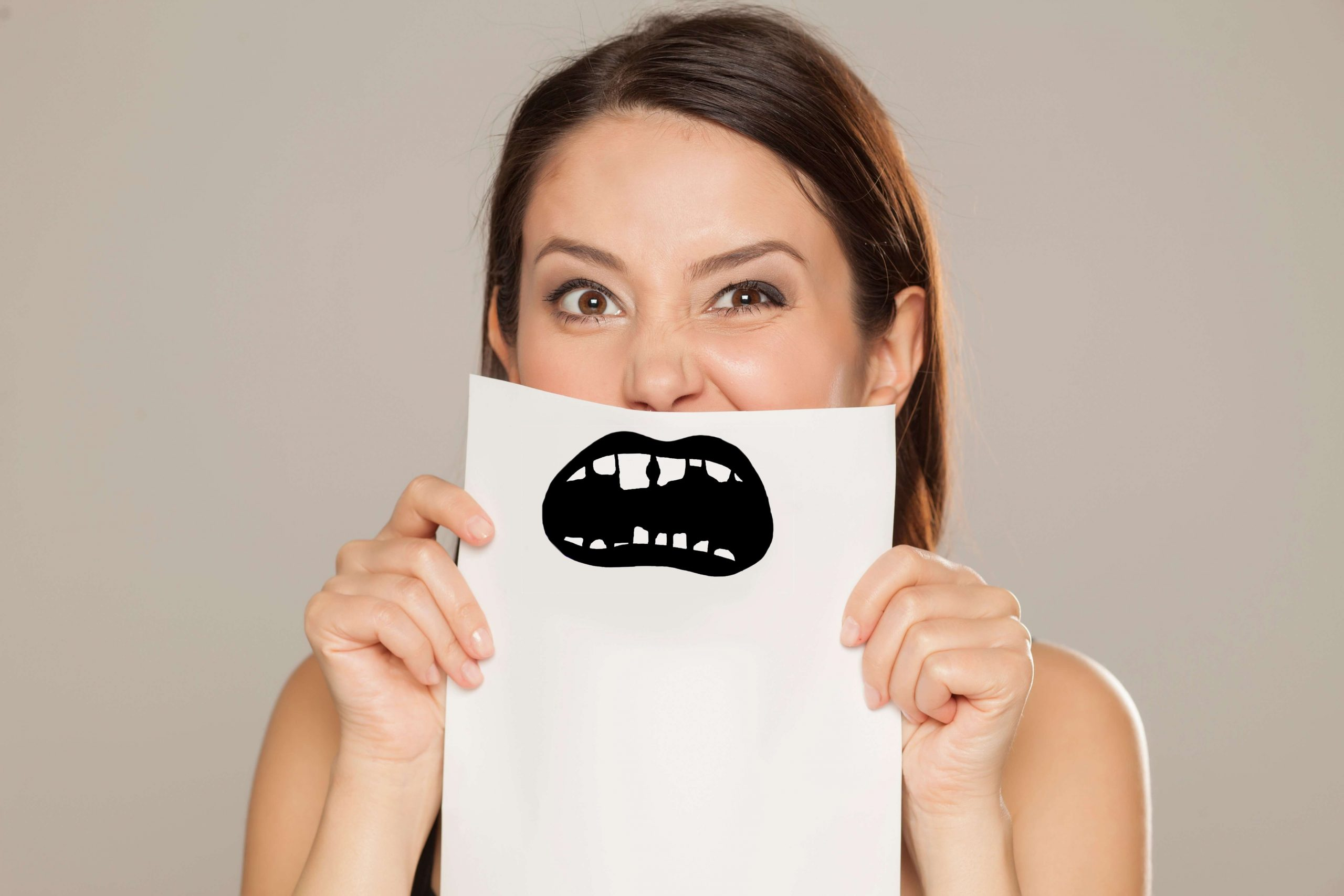 Woman holding up piece of paper with a drawing of a mouth with bad teeth