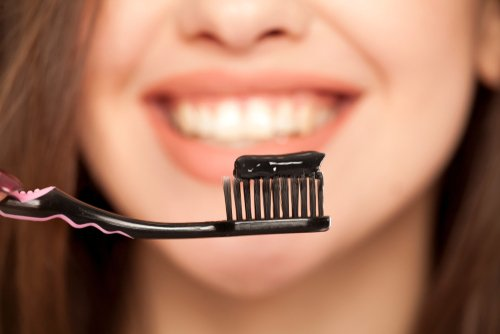 Charcoal toothaste on a black toothbrush with a smiling woman with white teeth in the background